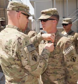 20th Engineer Brigade patch on right arm of the multicam uniform under the US flag as well as the left arm of the other soldier being pinned